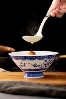 Tarro de sopa sobre un soporte de madera y una cuchara