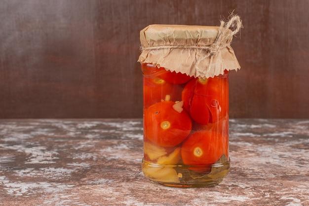 Tarro de tomates encurtidos caseros sobre mesa de mármol.