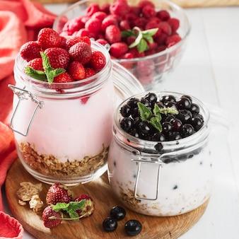 Tarro de yogur saludable con bayas frescas, avena y menta en mesa de madera. concepto de desayuno saludable