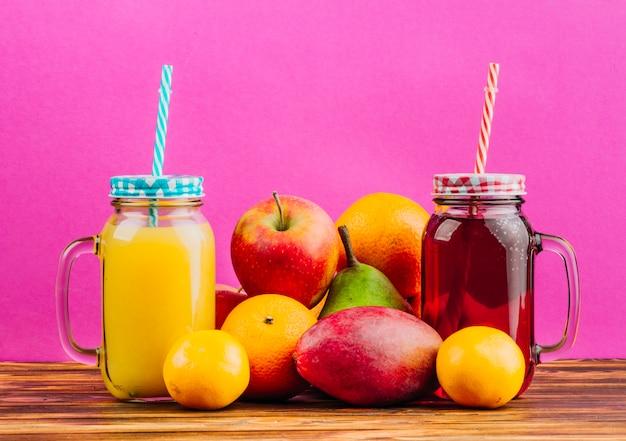 Tarros de albañil de jugo rojo y amarillo con pajitas y frutas frescas sobre fondo rosa