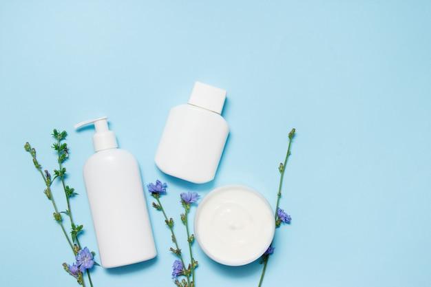 Tarros blancos de cosméticos con flores sobre un fondo azul