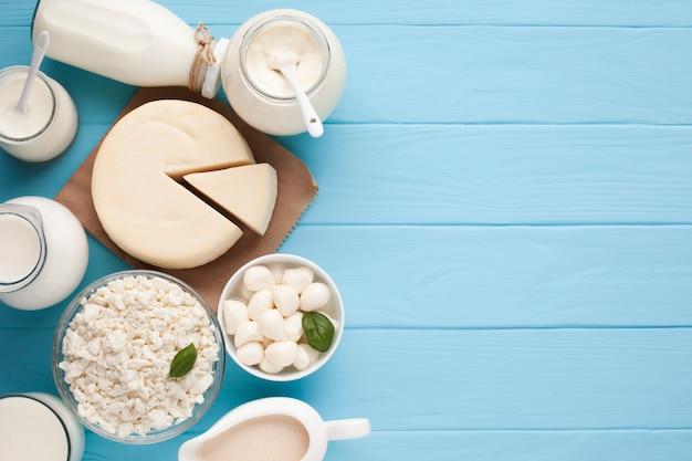 Tarros de leche y rueda de queso cortada.