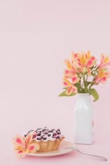 Tarta de arándanos con flor de alstroemeria sobre fondo rosa
