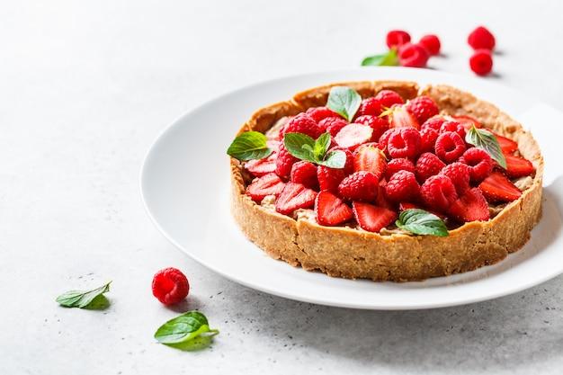 Tarta de bayas enteras con frambuesas, fresas y crema en un plato blanco