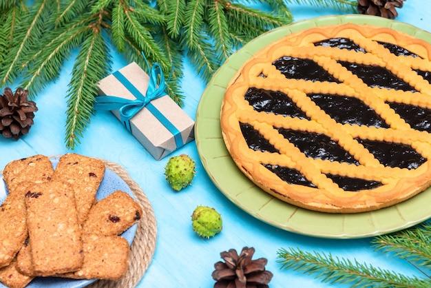 Tarta de bayas con mermelada en un feliz día de navidad. regalos y galletas.