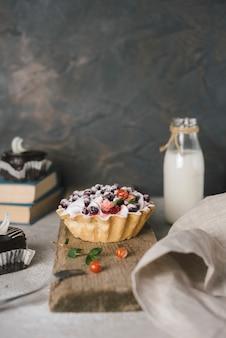 Tarta de bayas en tablero de madera con botella de leche