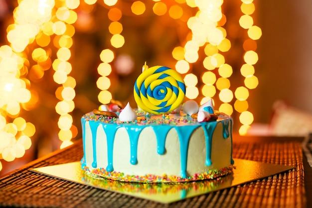 Tarta blanca de cumpleaños con dulces y velas para el pequeño bebé y decoraciones para aplastar el pastel