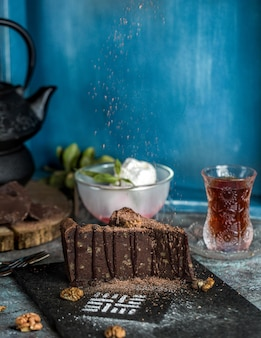 Tarta de brownie de chocolate con bolas de helado y un vaso de té