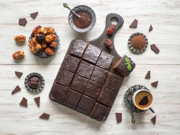 Tarta de brownie de chocolate con fechas en mesa de madera blanca
