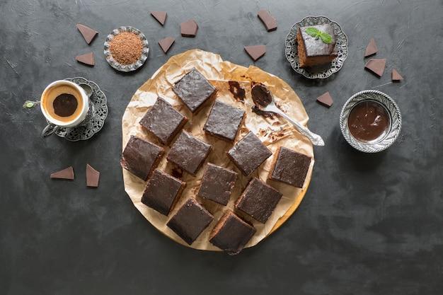 Tarta de brownie con fechas y taza de café, postre en mesa negra