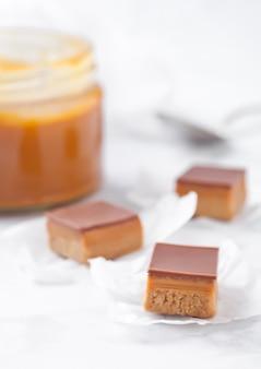 Tarta de caramelo y galleta mordida postre sobre tabla de mármol con tarro de caramelo salado