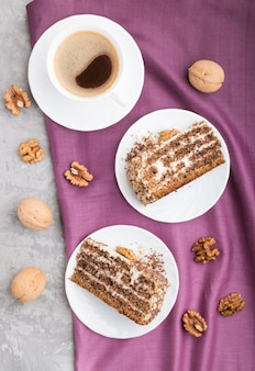 Tarta casera con crema de leche y nueces con una taza de café sobre una superficie de hormigón gris, vista superior.