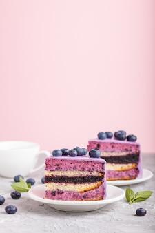 Tarta casera con crema de soufflé y mermelada de arándanos con una taza de café sobre fondo gris y rosa. vista lateral.
