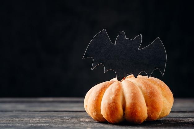 Tarta casera de halloween en forma de calabaza sobre fondo oscuro