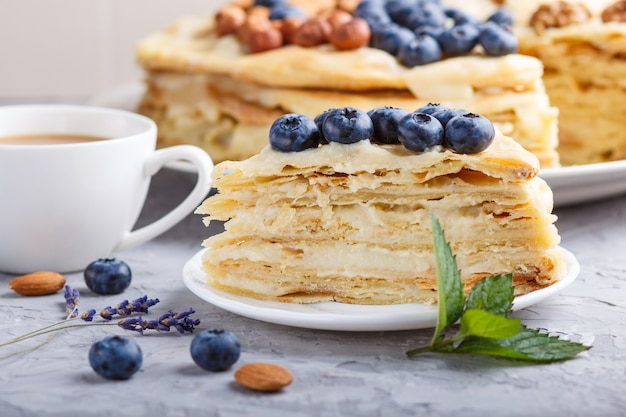 Tarta casera de napoleón en capas con crema de leche. decorado con arándanos, almendras, nueces, avellanas