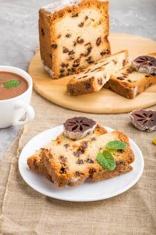 Tarta casera con pasas, caqui seco y una taza de chocolate caliente sobre un fondo de hormigón gris. vista lateral.