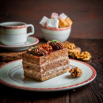 Tarta de chocolate con nuez y taza de té y azúcar en plato redondo