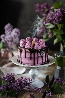 Tarta de chocolate y un ramo de lilas en mesa de madera