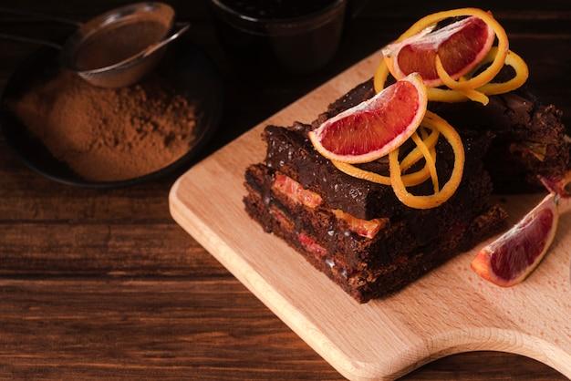 Tarta de chocolate sobre tabla de cortar con fruta