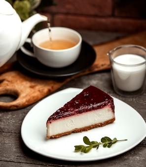 Tarta clásica de queso de bayas y una taza de té caliente