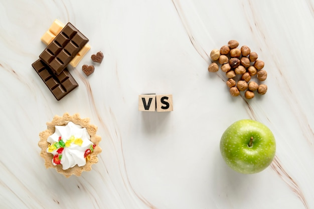 Tarta cremosa poco saludable; chocolate vs saludable avellana; manzana en el fondo de la textura