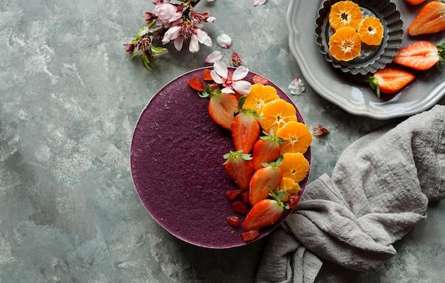 Tarta cruda vegana con frutas y semillas, decorada con flores.