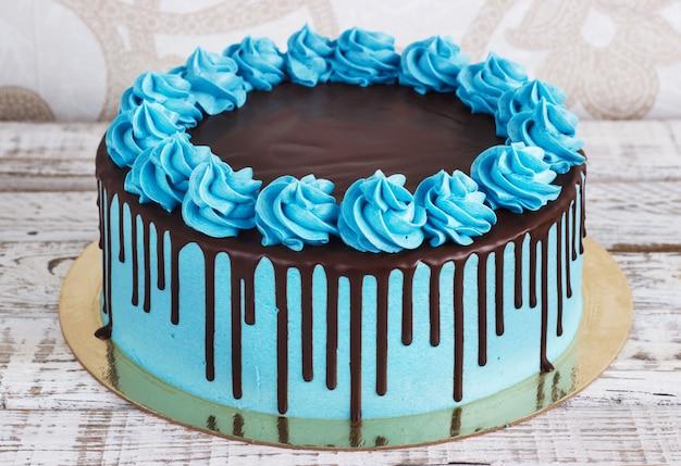 Tarta de cumpleaños con crema de chocolate gotea sobre un fondo blanco.