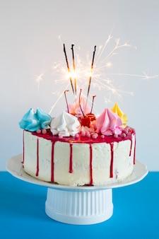 Tarta de cumpleaños con fuegos artificiales encendidos