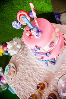 Tarta de cumpleaños rosa con caramelos y paletas