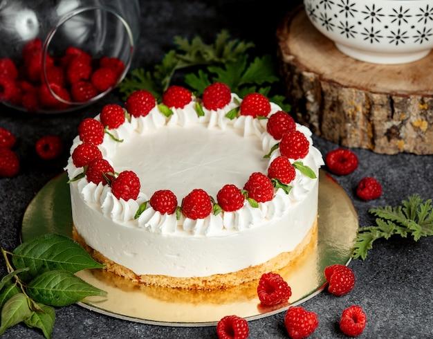 Tarta de frambuesa con crema blanca decorada con frambuesa y hojas de menta