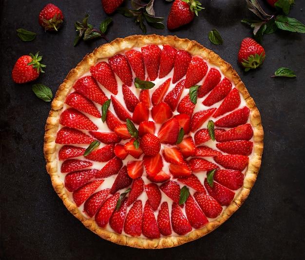Tarta de fresas y crema batida decorada con hojas de menta. vista superior