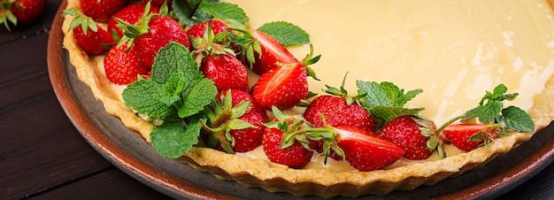 Tarta de fresas y crema batida decorada con hojas de menta