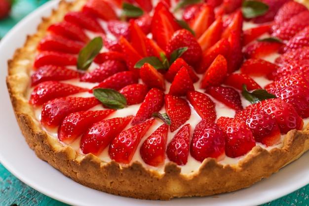 Tarta de fresas y crema batida decorada con hojas de menta.