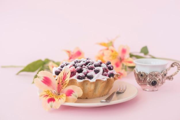 Tarta de frutas servida en un plato blanco con una flor de alstroemeria contra un fondo rosado
