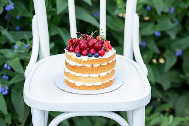 Tarta de galletas casera de verano con crema y bayas frescas en el jardín