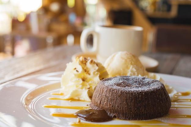 Tarta de lava de chocolate en un plato blanco con una taza de café en la cafetería