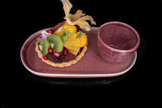 Tarta de limón y frutas mixtas y una taza de té