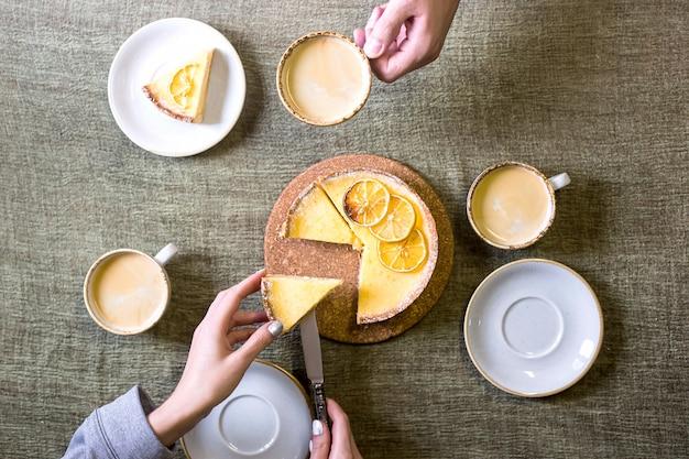 Tarta de limón sobre la mesa entre platillos y tazas de café.