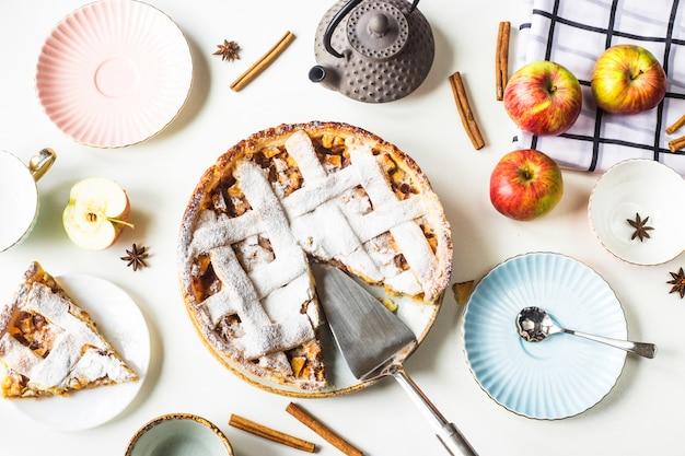 Tarta de manzana casera espolvoreada con azúcar en polvo con una rebanada