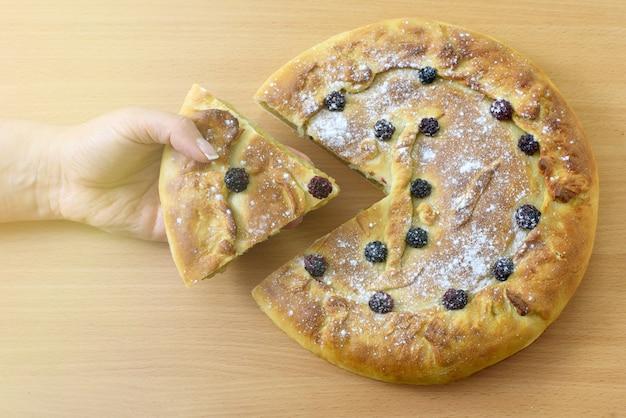 Tarta de manzana casera. la mano femenina toma un pedazo de pastel. vista superior