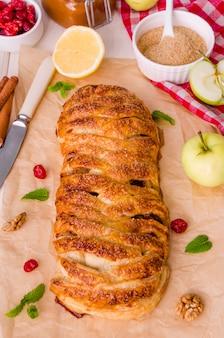 Tarta de manzana con cerezas secas, nueces, ralladura de limón y canela sobre fondo blanco de madera