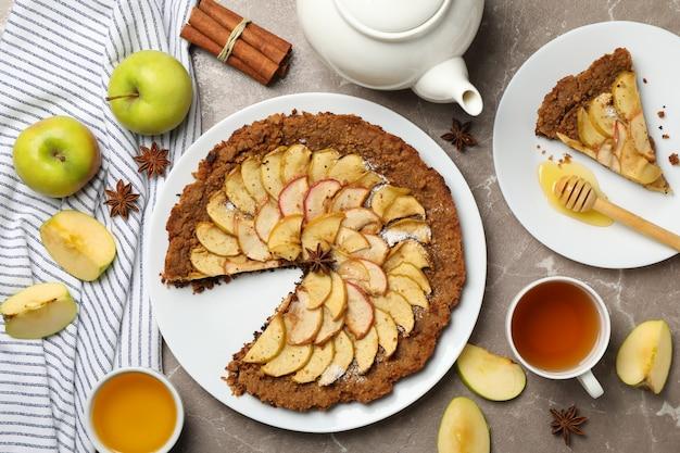 Tarta de manzana e ingredientes sobre fondo gris