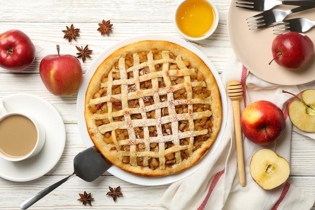 Tarta de manzana e ingredientes sobre fondo de madera