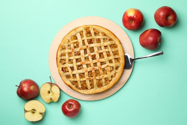 Tarta de manzana e ingredientes sobre fondo de menta