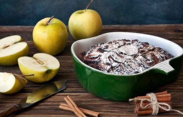 Tarta de manzana, manzanas frescas y palitos de canela sobre fondo de madera rústica