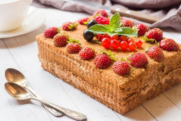 Tarta de miel con fresas, menta y grosellas
