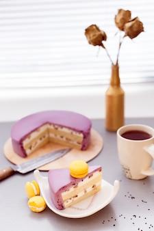 Tarta de mousse de grosellas y galleta con macarrones y café sobre una mesa en la cocina