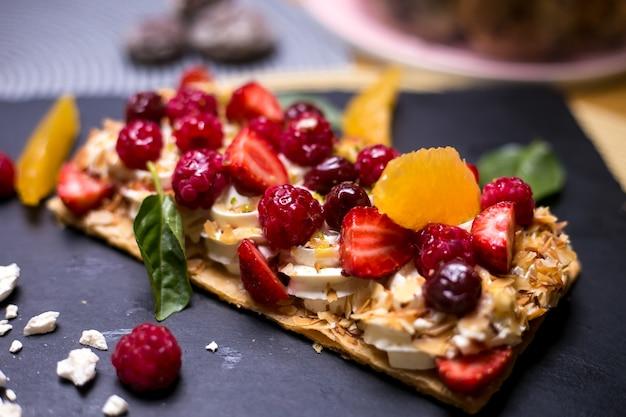 Tarta de napoleón con crema de frambuesa naranja malvaviscos cereza vista lateral de menta