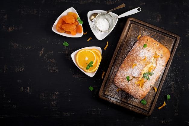 Tarta de naranja con albaricoques secos y azúcar en polvo