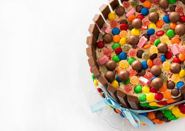 Tarta de piñata. dulces multicolores rellenos de pastel de cumpleaños con dulces dentro.